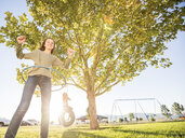 Girl spinning plastic hoop while friend swinging on tire swing at park during sunny day - CAVF49420