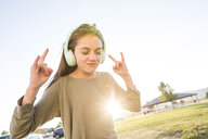 Girl with eyes closed gesturing horn sign while listening music on headphones at park against clear sky during sunset - CAVF49423