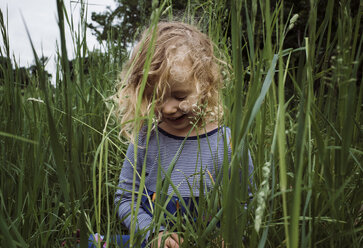 Close-up of happy girl sitting amidst grassy field. - CAVF49429
