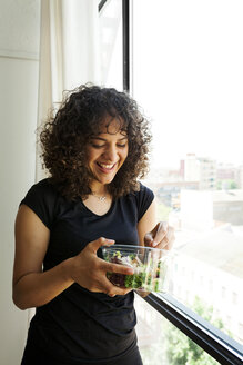 Happy woman eating salad while standing by window at home - CAVF49450