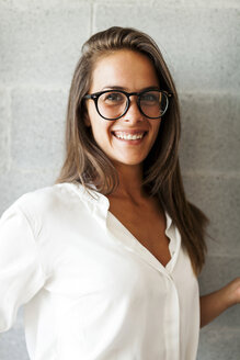 Portrait of happy woman wearing eyeglasses while standing by wall at home - CAVF49468