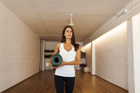 Thoughtful woman looking away while holding exercise mat in yoga class - CAVF49480