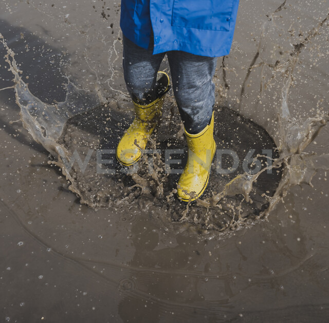 Low section of playful boy wearing rubber boots while splashing puddle - CAVF49527