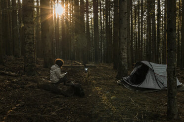 Woman using mobile phone while sitting at campsite in forest during sunset - CAVF49545