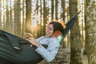 Woman using smart phone while lying on hammock in forest during sunset - CAVF49548