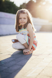 Portrait of girl holding chalk while crouching on street - CAVF49554