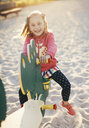 High angle portrait of happy girl playing on seesaw in playground - CAVF49557
