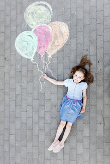 High angle portrait of happy girl lying by colorful balloons drawing on street - CAVF49560