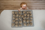 High angle view of cute baby boy eating cookies by table at home - CAVF49599