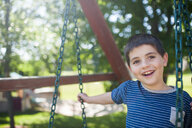 Portrait of happy boy swinging at yard - CAVF49602