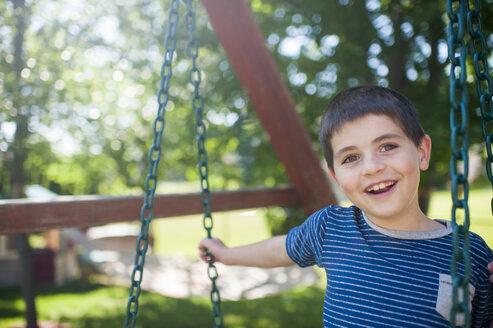 Portrait of happy boy swinging at yard - CAVF49602