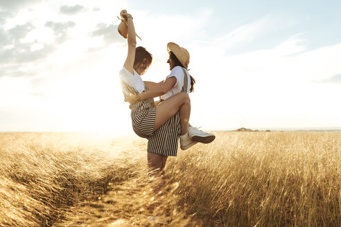 Happy woman carrying twin sister while standing on grassy field against sky - CAVF49608