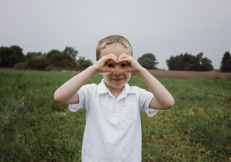Portrait of boy making heart shape while standing on grassy field against sky at park - CAVF49614