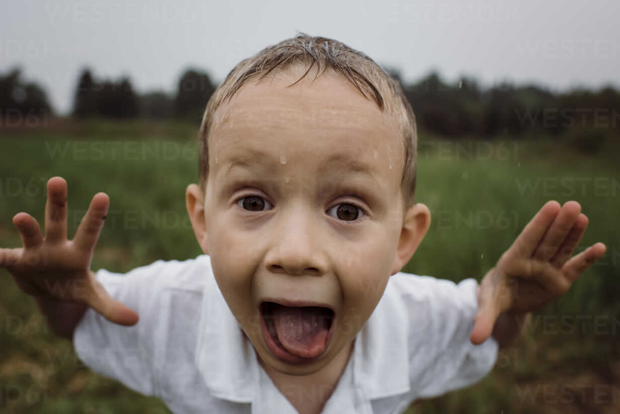 Portrait of wet boy screaming while standing against sky at park during rainy season - CAVF49620 - Cavan Images/Westend61