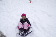 High angle view of cheerful girl sitting on sled during winter - CAVF49635