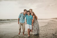 Portrait of happy siblings standing at beach against sky during sunset - CAVF49653