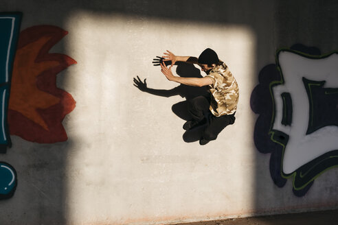 Man doing breakdance in urban concrete building, jumping against wall with graffitis - JRFF01909