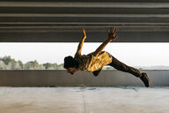 Man doing breakdance in urban concrete building, jumping mid air - JRFF01912