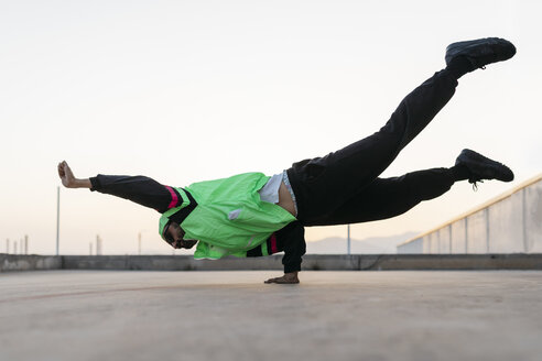 Man doing breakdance in urban concrete building, standing on hand - JRFF01915