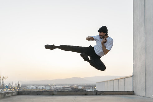 Man doing breakdance in urban concrete building, jumping mid air - JRFF01918