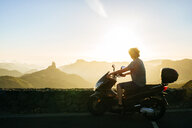 Spain, Canary Islands, Gran Canaria, man on motor scooter watching sunset over mountainscape - KIJF02064