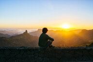 Spain, Canary Islands, Gran Canaria, back view of man sitting on a wall watching sunset over mountainscape - KIJF02067