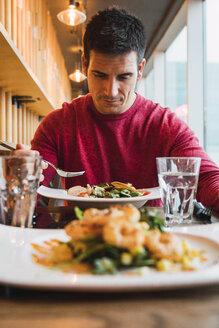 Businessman eating salad in a restaurant - KKAF02436