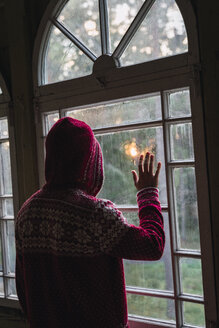 Back view of man wearing hooded jacket looking out of window - KKAF02449
