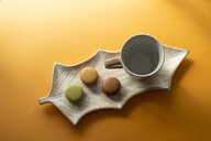 Three Macarons and an empty cup on a leaf-shaped platter - AFVF01840