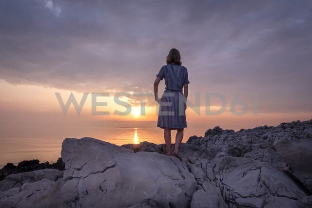 Croatia, Istria, Losinj, woman standing on rocky coast at sunset - HAMF00519 - Hans Mitterer/Westend61