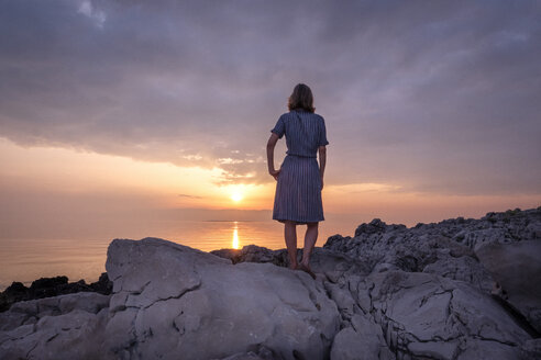 Croatia, Istria, Losinj, woman standing on rocky coast at sunset - HAMF00519