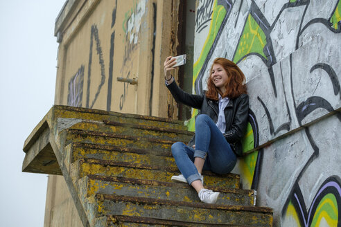 Italy, Finale Ligure, redheaded teenage girl ltaking selfie in front of graffiti wall - LBF02128