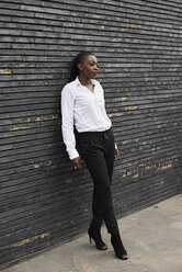 Portrait of smart businesswoman  wearing white shirt and black trousers leaning against wall - IGGF00668