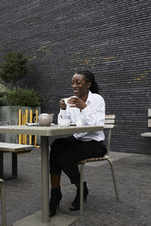 Laughing businesswoman sitting on  terrace of a coffee shop drinking tea - IGGF00677