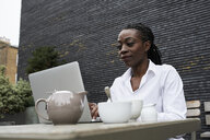 Portrait of smiling businesswoman sitting on terrace of a coffee shop working on laptop - IGGF00680