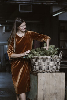 Smiling young woman with wickerbasket of vegetables wearing brown dress of velvet - ALBF00641