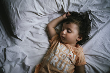 Baby girl sleeping on bed with t-shirt message 'Dreams do come true' - GEMF02421