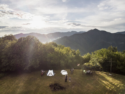 Italy, Tuscany, Pistoia, father and son on a meadow next to tent and motorbike - FBAF00117
