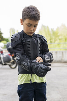 Boy putting on protective clothing preparing for a motorbike trip - FBAF00123