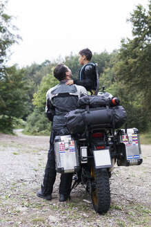 Father and son having a break during a motorbike trip - FBAF00135