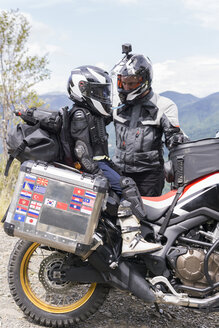 Father and son having a break during a motorbike trip - FBAF00144
