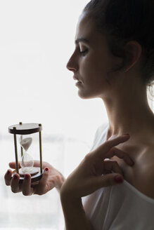 Young woman holding an hourglass against a bright window - JPTF00030