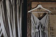 Grey dress hanging at wooden door - ALBF00662