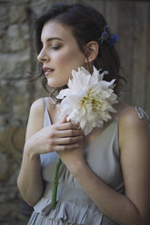 Young woman wearing grey dress holding a flower - ALBF00671