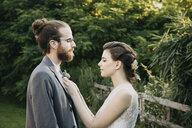Bride adjusting groom's suit outdoors - ALBF00674