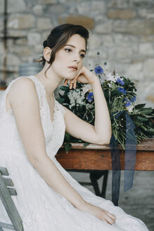 Pensive young woman wearing wedding dress sitting at table - ALBF00683