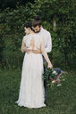 Bride and groom standing on meadow embracing - ALBF00689