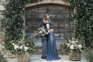 Bride and groom standing at a wooden gate embracing - ALBF00692