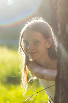 Portrait of smiling girl in nature at backlight - SARF03951