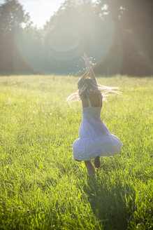 Happy girl dancing on summer meadow at backlight - SARF03954